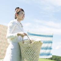 洗濯物を持ち微笑む女性 20027010147| 写真素材・ストックフォト・画像・イラスト素材|アマナイメージズ