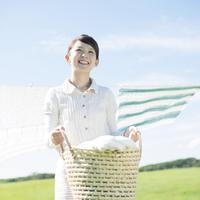 洗濯物を持ち微笑む女性 20027010148| 写真素材・ストックフォト・画像・イラスト素材|アマナイメージズ