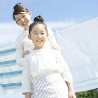 洗濯物の前で微笑む親子 20027010156| 写真素材・ストックフォト・画像・イラスト素材|アマナイメージズ