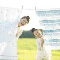 洗濯物の後ろから顔を出す親子 20027010167| 写真素材・ストックフォト・画像・イラスト素材|アマナイメージズ