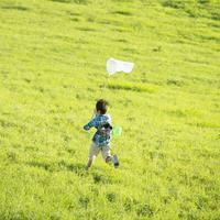 草原を走る男の子の後姿
