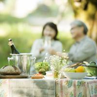 テーブルの上に並ぶ料理と乾杯をするシニア夫婦