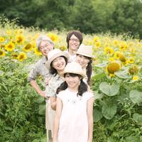 ヒマワリ畑で微笑む3世代家族