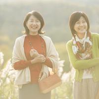 ススキの前で微笑む2人のシニア女性