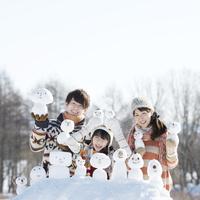 雪だるまを持ち微笑む家族