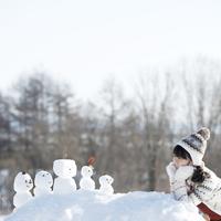 頬杖をつき雪だるまを見る女の子