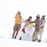 雪だるまのまわりで手をつなぐ若者たち