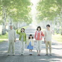 白樺並木で手を振る3世代家族