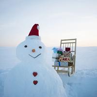 サンタ帽を被った雪だるまとソリ