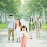 白樺並木で微笑む3世代家族
