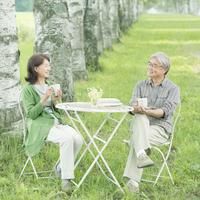 白樺並木でコーヒーを飲むシニア夫婦