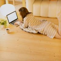 床に寝転びパソコン操作をする女性