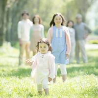 新緑の中で微笑む女の子と家族