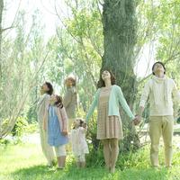 ポプラの木を囲み手をつなぐ3世代家族
