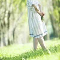 野花を持ちポプラ並木を歩く女性
