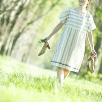 靴を持ちポプラ並木を歩く女性