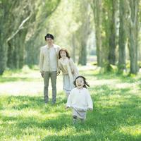 ポプラ並木を走る女の子と見守る両親