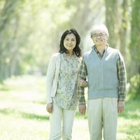 ポプラ並木で腕を組むシニア夫婦