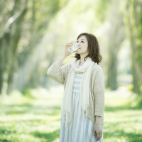 ポプラ並木で水を飲む女性