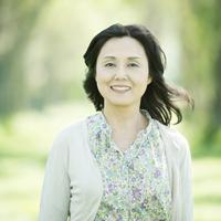 新緑の中で微笑むシニア女性