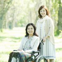 車椅子で散歩をするシニア女性と娘