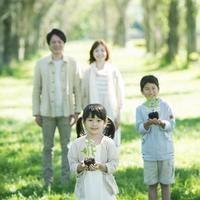 植物の苗を持つ兄妹と見守る両親