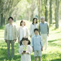植物の苗を持つ女の子と見守る家族