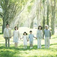ポプラ並木で手をつなぐ3世代家族