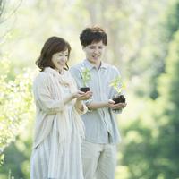 植物の苗を持ち微笑むカップル
