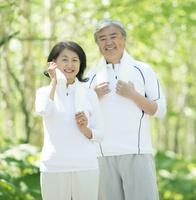 自然の中で汗を拭うシニア夫婦