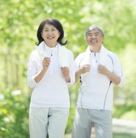 自然の中でジョギングをするシニア夫婦
