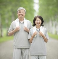 白樺並木でジョギングをするシニア夫婦