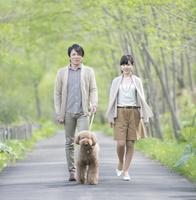 公園で犬の散歩をするミドル夫婦