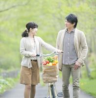 公園で自転車を押すミドル夫婦