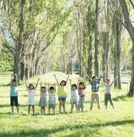 ポプラ並木で両手を挙げる子供たち