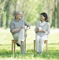 ポプラ並木で椅子に座りコーヒーを飲むシニア夫婦