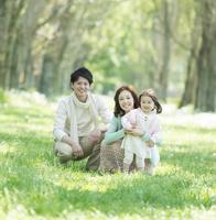 新緑の中で子供を抱き微笑む家族