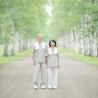 白樺並木で微笑むシニア夫婦