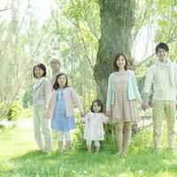ポプラの木の側で微笑む3世代家族