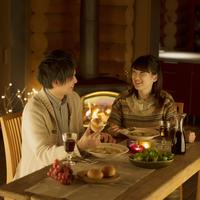 暖炉の前で夕食を食べるカップル