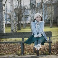 ベンチに座り微笑む女性