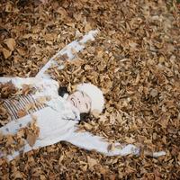 落ち葉の上に寝転ぶ女性