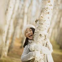 木に抱きつき微笑む女性