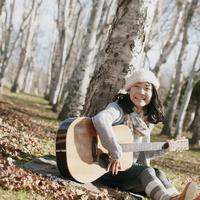 木に寄りかかりギターを弾く女性
