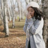 木に寄りかかり手を温める女性 20027011025| 写真素材・ストックフォト・画像・イラスト素材|アマナイメージズ