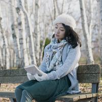 ベンチに座り本を持つ女性