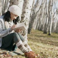 木に寄りかかり読書をする女性