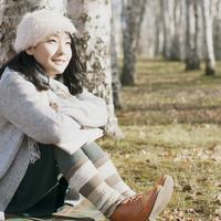 木に寄りかかり微笑む女性