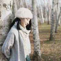 木に寄りかかりうつむく女性 20027011077| 写真素材・ストックフォト・画像・イラスト素材|アマナイメージズ