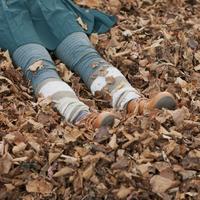 落ち葉の上に寝転ぶ女性の足元